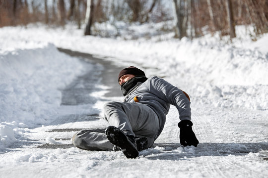 Mann liegt verletzt auf der Straße, Sturz im Winter durch Glatteis und Schnee