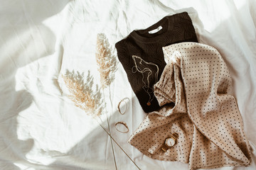 Obraz Woman trendy fashion clothes on white linen bed. Flat lay, top view. Black sweater, silk skirt with polka dots, gold necklace, watch, earrings, reeds. Feminine french style concept. - fototapety do salonu