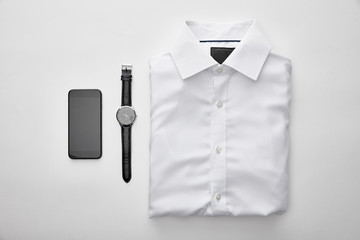 flat lay with plain white folded shirt near smartphone and watches on white background
