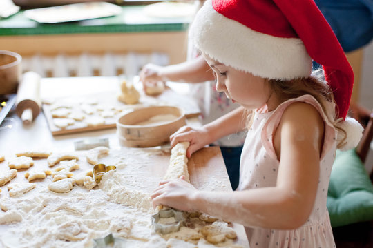 Kids cooking Christmas cookies in cozy kitchen. Child prepares holiday food for family. Cute little girls bake homemade festive gingerbreads. Lifestyle moment. Santa helper. Children chef concept