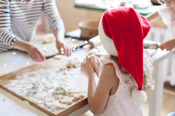 Family is cooking Christmas cookies in cozy kitchen. Kid prepare holiday food for family together. Cute girls bake homemade festive gingerbreads. Lifestyle moment. Santa helpers. Children chef concept