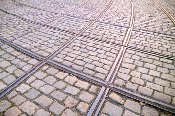 kreuzung von alten eingedeckten straßenbahngleisen im straßenpflaster