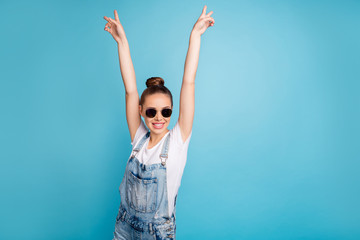 Portrait of funny funky girl with eyeglasses eyewear raising v-signs wearing white t-shirt denim jeans overalls isolated over blue background