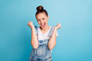 Portrait of delighted woman with her eye closed raising fists shouting yeah wearing white t-shirt denim jeans isolated over blue background