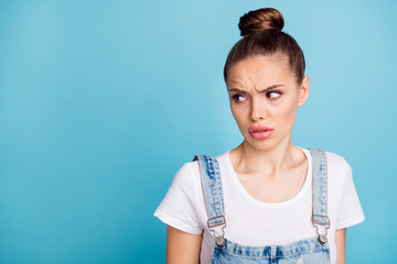 Portrait of upset person looking at copy space grimacing wearing white t-shirt denim jeans isolated over blue background