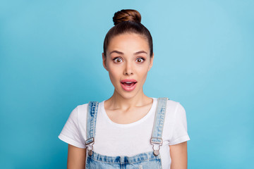Close up photo of astonished person looking with opened mouth wearing white t-shirt denim jeans overalls isolated over blue background