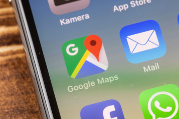 METTINGEN, GERMANY - NOVEMBER 9, 2018: Close up to google maps app on the screen of an iPhone X with personalized background