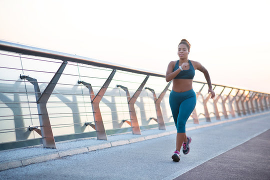 Dark-skinned young overweight woman running really fast