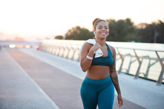 Tattooed young woman going home after running in the morning