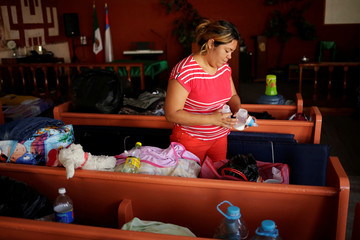 Jennifer, a migrant mother from El Salvador returned to Mexico to await her U.S. asylum hearing, prepares a feeding bottle for her son at Casa del Migrante migrant shelter in Ciudad Juarez
