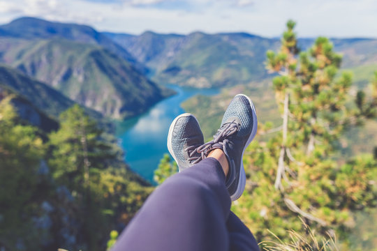 Female feet selfie on the top of the hill enjoying the view on river or lake canyon. Freedom concept.