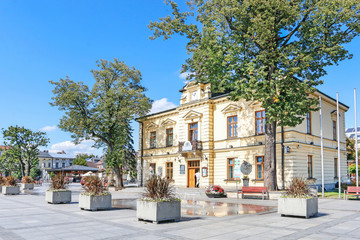 Fototapeta NOWY TARG, POLAND - SEPTEMBER 12, 2019: City hall building and fountain in front of it at the market square obraz