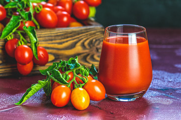 Glass of fresh delicious jummy red tomato juice and fresh tomatoes in wooden box. Dark background. Close up. Gmo free. Natural good food
