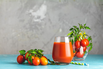 Glass of fresh delicious jummy red tomato juice and fresh tomatoes on light concrete surface. Close up. Gmo free. Natural good food