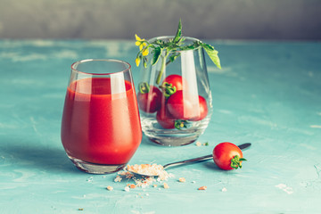 Glasses of fresh delicious jummy red tomato juice and fresh raw tomatoes with pink salt in spoon on light concrete surface. Close up. Gmo free. Natural good food