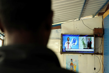 A man looks at a television screen broadcasting news at a local bar in Addis Ababa
