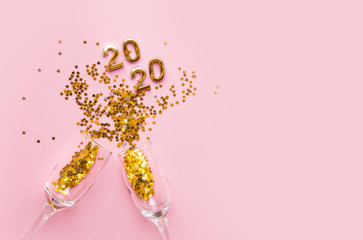 Flatlay Christmas composition on a pastel pink background. Glasses with champagne, confetti. Christmas Eve 2020.