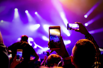 Smartphone in hands during music show.