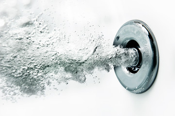A nozzle blows air under water in a bath tub.