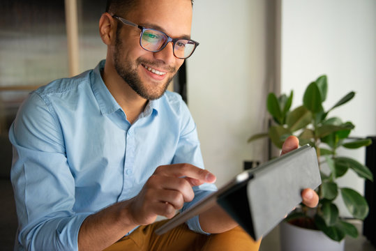 Young smiling Man typing on digital tablet