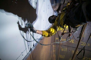Close up picture of rope access painter working at height abseiling upside down wearing safety chemical protective mask  commencing spray painting in confined space construction site Perth, Australia