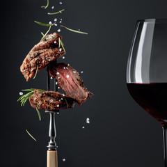 Spoed Foto op Canvas Wijn Grilled ribeye beef steak with rosemary on a black background.