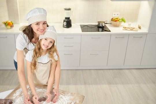 Cute daughter and mother in aprons baking cookies at kitchen