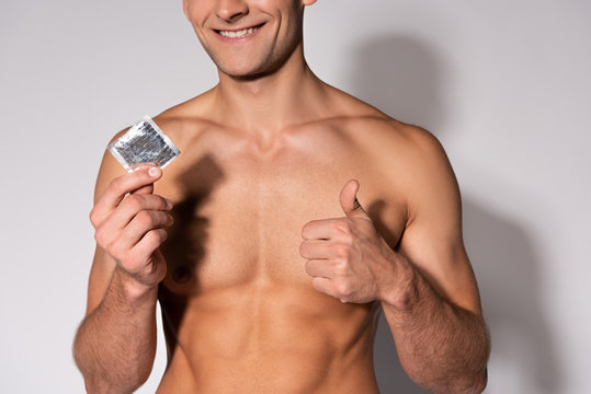 cropped view of cheerful and muscular man showing thumb up while holding condom on white