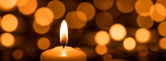 Burning candle in front of bokeh background