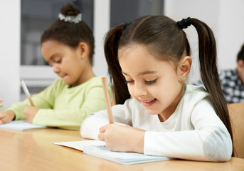 Happy student sitting at table and writing in copybook