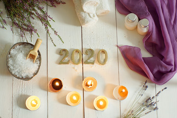 Foto op Aluminium Spa Metallic numbers 2020 on a background of white boards next to towels and sea salt for spa treatments, scented candles and a sprig of heather and lavender lie nearby