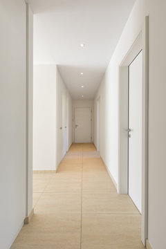 Corridor with travertine floor, white walls and built-in wardrobes