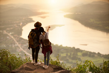 couple backpacker standing on cliff with sunset background