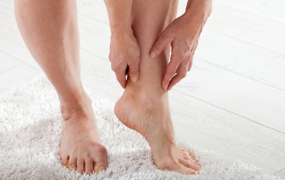 Middle-aged woman suffering from pain in leg at home, closeup. Physical injury concept.