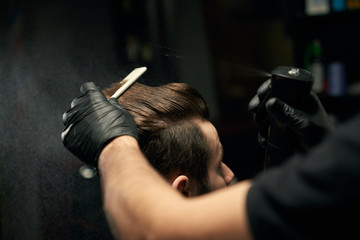 Crop of barber hands making new haircut for male client