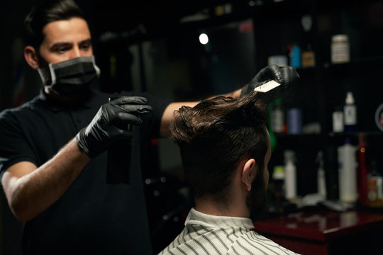 Male professional barber doing hair styling to handsome guy