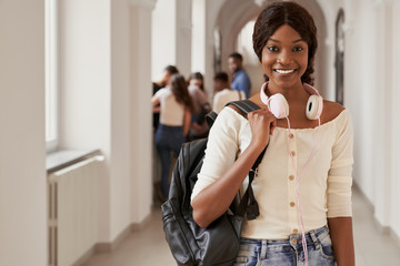 African girl looking at camera with group of students behind