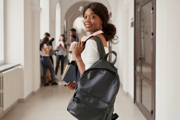 African girl smiling and looking at camera in college hall