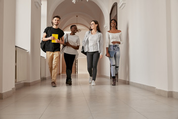 Mixed-race group of students walking throuth the corridor