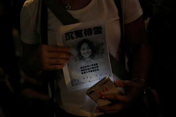 A woman holds a picture of a teenage female protester, whom protesters claim was killed by police, at her memorial site at Sheung Shui district in Hong Kong