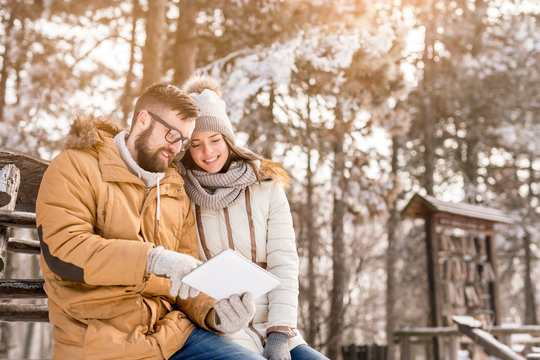 Couple using tablet on winter vacation