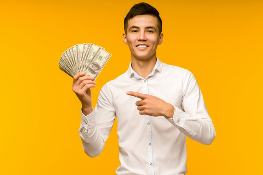 Joyful asian man in a white shirt points a finger at money dollars on a yellow background