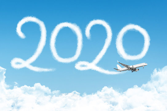Happy New year 2020 concept travel on the background below cloudscape. Drawing by passenger airplane vapor contrail in sky.