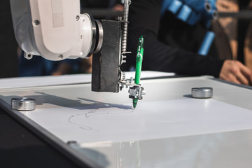 Robotic hand draws a picture with a green pen. Science and high technologies concept.