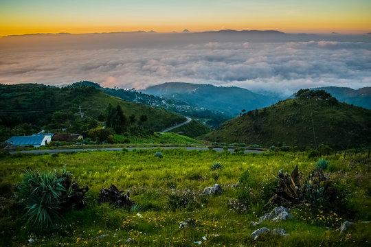 paisaje de campos verde y nubes emergiendo entre el valle