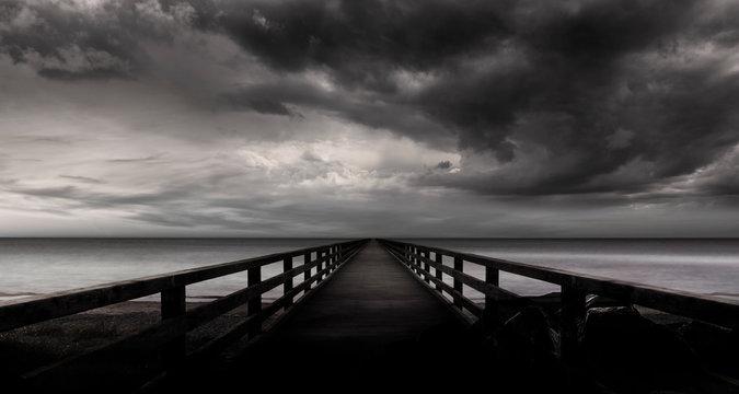 Steg ins Wasser mit Sturmwolken bei stürmischer See