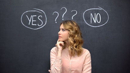 Puzzled woman choosing between yes no, stereotype of uncertain female thinking
