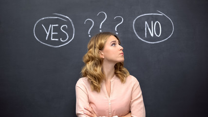 Uncertain female choosing between yes no, standing against blackboard, dilemma