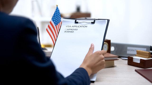 Female immigration inspector denying visa application, american flag on table