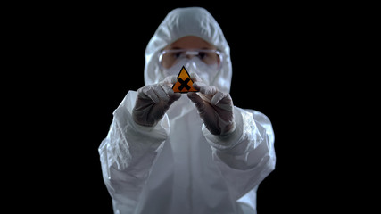 Lab worker in protective suit showing cross symbol against dark background